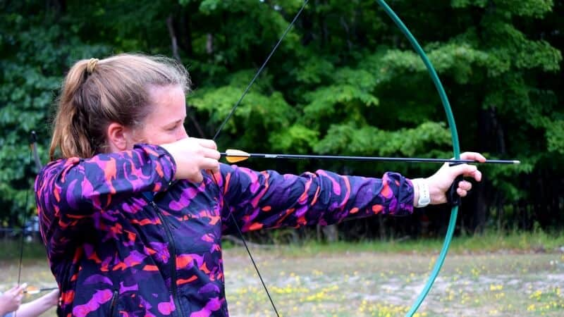 Girl aiming with bow and arrow