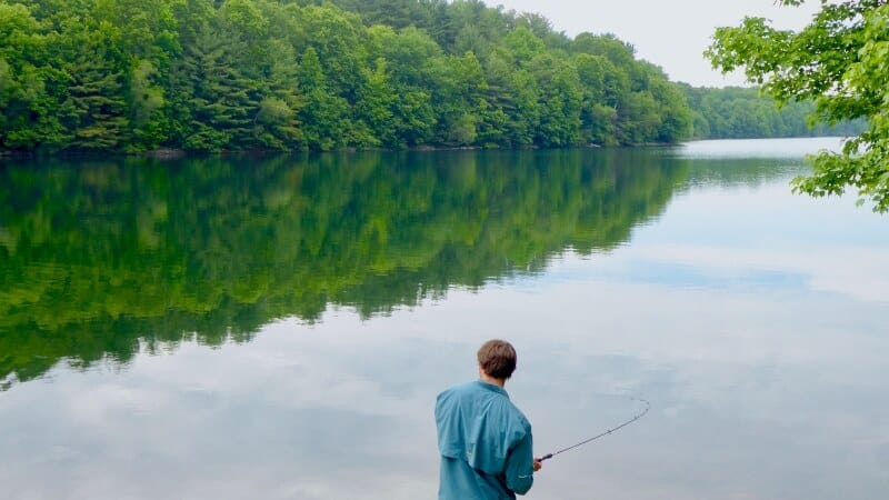 Man Fishing and Green Trees