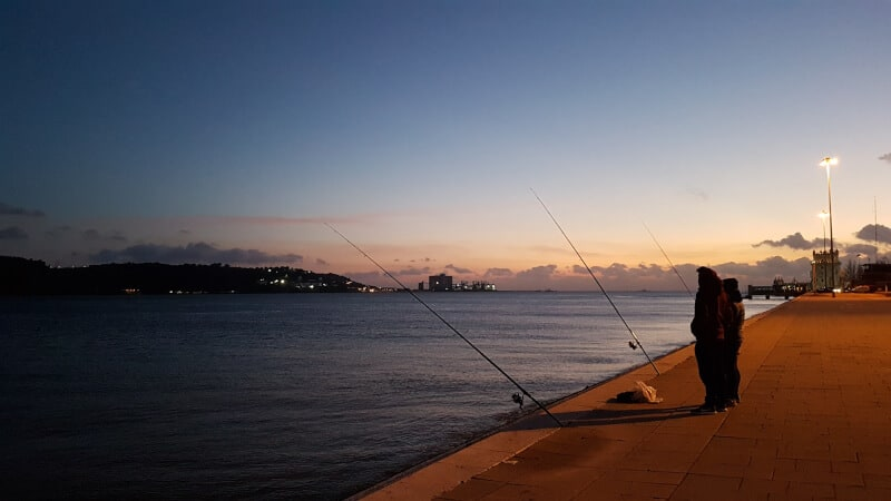 Two people near waters with big fishing rod