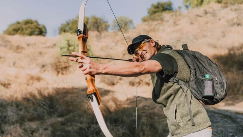 smiling man while shooting a bow