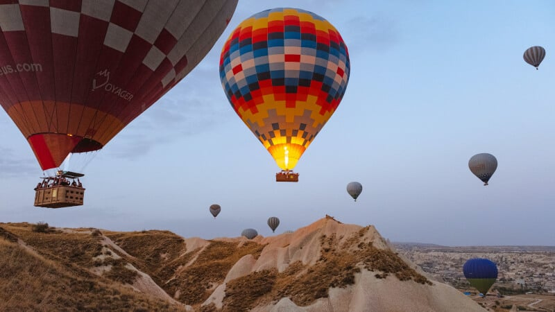hot air balloons above mountain
